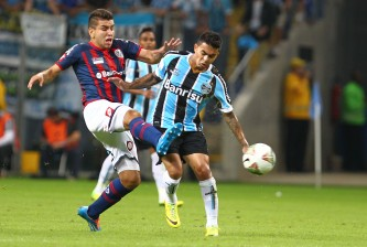 PORTO ALEGRE, BRAZIL - APRIL 30: Dudu of Gremio, battles fo the ball against Angel Correa, of San Lorenzo during the match between Gremio and San Lorenzo for the Copa Briedgestone Libertadores 2014 at Arena do Gremio stadium on April 30, 2014 in Porto Alegre, Brazil. (Photo by Lucas Uebel/Getty Images)