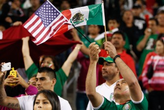 SEATTLE, WA - JULY 11:  A fan of Mexico waves flags during the match against Canada at CenturyLink Field on July 11, 2013 in Seattle, Washington.  (Photo by Otto Greule Jr/Getty Images)
