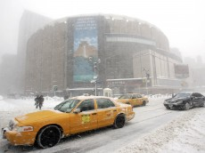 NEW YORK - FEBRUARY 12:  Vehicles drive past Madison Square Garden during a snow storm prior to a game between St. John's University and Syracuse University on February 12, 2006 at Madison Square Garden in New York City.  (Photo by Ned Dishman/Getty Images)