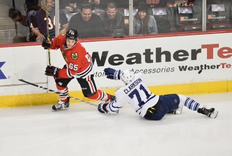 CHICAGO, IL - DECEMBER 21:  Andrew Shaw #65 of the Chicago Blackhawks (L) dodges a check from David Clarkson #71 of the Toronto Maple Leafs during the third period at the United Center on December 21, 2014 in Chicago, Illinois. The Blackhawks defeated the Maple Leafs 4-0. (Photo by Brian Kersey/Getty Images)