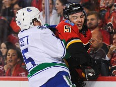 CALGARY, AB - OCTOBER 7: Mark Giordano #5 of the Calgary Flames gets checked by Derek Dorsett #15 of the Vancouver Canucks in the NHL season opener at Scotiabank Saddledome on October 7, 2015 in Calgary, Alberta, Canada. (Photo by Derek Leung/Getty Images)