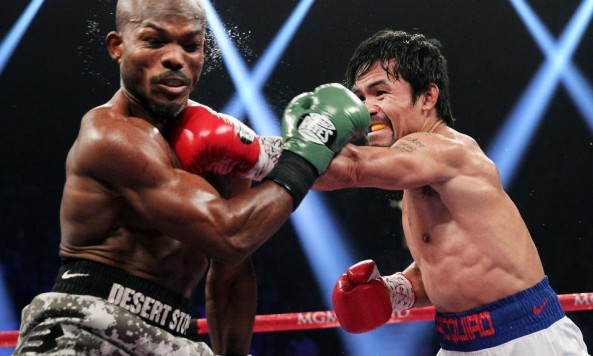 Manny Pacquiao (right) connects on Tim Bradley (photo credit: Chris Farina, Top Rank)