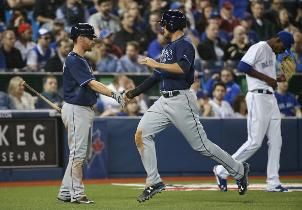 TORONTO, CANADA - APRIL 14: Steven Souza Jr. #35 of the Tampa Bay Rays is congratulated by Logan Forsythe #11 after scoring the go-ahead run in the eighth inning during MLB game action as Miguel Castro #51 of the Toronto Blue Jays looks on on April 14, 2015 at Rogers Centre in Toronto, Ontario, Canada. (Photo by Tom Szczerbowski/Getty Images)