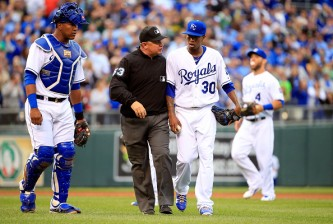KANSAS CITY, MO - APRIL 18:  Pitcher Yordano Ventura #30 of the Kansas City Royals is escorted off the field by umpire Greg Gibson #53 after hitting Brett Lawrie #15 of the Oakland Athletics with a pitch during the 4th inning of the game at Kauffman Stadium on April 18, 2015 in Kansas City, Missouri.  (Photo by Jamie Squire/Getty Images)