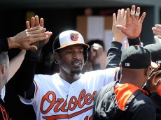 BALTIMORE, MD - APRIL 26: Adam Jones #10 of the Baltimore Orioles celebrates with teammates after scoring in the third inning against the Boston Red Sox at Oriole Park at Camden Yards on April 26, 2015 in Baltimore, Maryland.  (Photo by Greg Fiume/Getty Images)