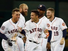 :HOUSTON, TX - APRIL 30: Jose Altuve #27 of the Houston Astros gets mobbed by his teammates after his tenth inning game-winning RBI single to defeat the Seattle Mariners 3-2 at Minute Maid Park on April 30, 2015 in Houston, Texas. (Photo by Scott Halleran/Getty Images)