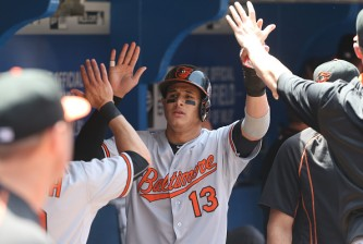 TORONTO, CANADA - JUNE 20: Manny Machado #13 of the Baltimore Orioles is congratulated by teammates in the dugout after scoring a run in the first inning during MLB game action against the Toronto Blue Jays on June 20, 2015 at Rogers Centre in Toronto, Ontario, Canada. (Photo by Tom Szczerbowski/Getty Images)