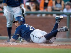 SAN FRANCISCO, CA - JULY 28:  Carlos Gomez #27 of the Milwaukee Brewers dives into home plate to score a run against the San Francisco Giants during the first inning at AT&T Park on July 28, 2015 in San Francisco, California.  (Photo by Jason O. Watson/Getty Images)