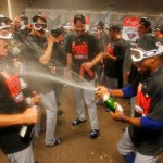 CINCINNATI, OH - SEPTEMBER 27: Curtis Granderson #3 of the New York Mets spray champagne on Bob Geren #15 as they celebrate in the clubhouse after defeating the Cincinnati Reds 10-2 to clinch the National League East Championship at Great American Ball Park on September 26, 2015 in Cincinnati, Ohio.  (Photo by John Sommers II/Getty Images)