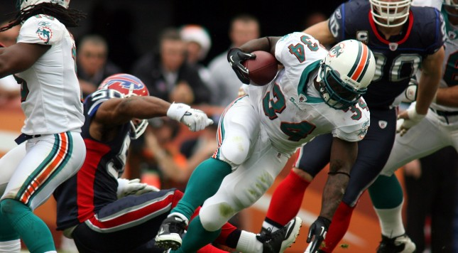 MIAMI, FL - DECEMBER 19:  Running back Ricky Williams #34 of the Miami Dolphins is upended by cornerback Donte Whitner #20 of the Buffalo Bills during a game at Sun Life Stadium on December 19, 2010 in Miami, Florida. The Bills defeated the Dolphins 17-14. (Photo by Marc Serota/Getty Images)