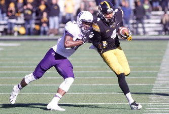 IOWA CITY, IA - NOVEMBER 01:  Wide receiver Tevaun Smith #4 of the Iowa Hawkeyes runs up the field in front of cornerback Matthew Harris #27 of the Northwestern Wildcats on November 1, 2014 at Kinnick Stadium in Iowa City, Iowa.  (Photo by Matthew Holst/Getty Images)