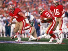 STANFORD, CA - JANUARY 20:  Running back Roger Craig #33 of the San Francisco 49ers follows his blocker offensive guard Randy Cross #51 in Super Bowl XIX against the Miami Dolphins at Stanford Stadium on January 20, 1985 in Stanford, California. The 49ers won 38-16. (Photo by George Rose/Getty Images)
