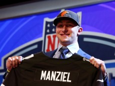 NEW YORK, NY - MAY 08:  Johnny Manziel of the Texas A&M Aggies poses with a jersey after he was picked #22 overall by the Cleveland Browns during the first round of the 2014 NFL Draft at Radio City Music Hall on May 8, 2014 in New York City.  (Photo by Elsa/Getty Images)