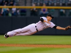 DENVER, CO - SEPTEMBER 6:  Shortstop Josh Rutledge #14 of the Colorado Rockies makes a diving catch for the first out of the third inning against the San Diego Padres at Coors Field on September 6, 2014 in Denver, Colorado. (Photo by Justin Edmonds/Getty Images)