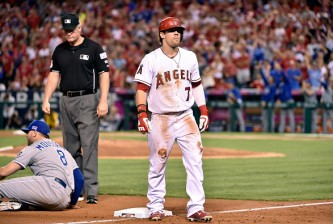 ANAHEIM, CA - OCTOBER 03:  Collin Cowgill #7 of the Los Angeles Angels reacts after being tagged out at third base in the eighth inning by Mike Moustakas #8 of the Kansas City Royals during Game Two of the American League Division Series at Angel Stadium of Anaheim on October 3, 2014 in Anaheim, California.  (Photo by Denis Poroy/Getty Images)