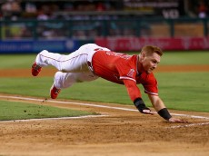 ANAHEIM, CA - SEPTEMBER 12:  Kole Calhoun #56 of the Los Angeles Angels of Anaheim dives into home against the Houston Astros at Angel Stadium of Anaheim on September 12, 2014 in Anaheim, California.  (Photo by Jeff Gross/Getty Images)