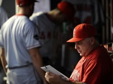 NEW YORK - SEPTEMBER 14: Manager Mike Scioscia #14 of the Los Angeles Angels of Anaheim reviews a lineup card prior to a game against the New York Yankees at Yankee Stadium on September 14, 2009 in the Bronx borough of New York City.  (Photo by Jeff Zelevansky/Getty Images)