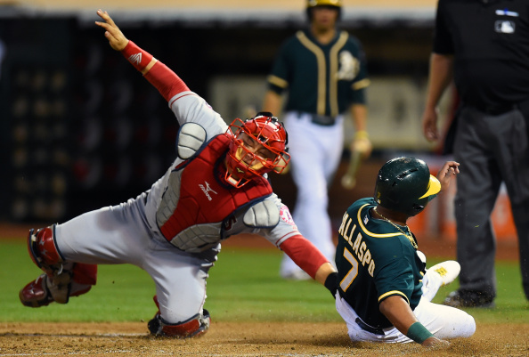 OAKLAND, CA - AUGUST 22:  Alberto Callaspo #7 of the Oakland Athletics slides into home to score, beating the tag of Hank Conger #24 of the Los Angeles Angels of Anaheim in the bottom of the six inning at O.co Coliseum on August 22, 2014 in Oakland, California. Callaspo scored from first base on an rbi triple from Sam Fuld #23. (Photo by Thearon W. Henderson/Getty Images)