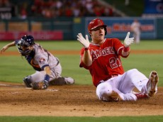 ANAHEIM, CA - SEPTEMBER 12:  Mike Trout #27 of the Los Angeles Angels of Anaheim slides safely past catcher Jason Castro #15 of the Houston Astros and scores a run on a catching error by shortstop Jonathan Villar (not pictured) in the fourth inning at Angel Stadium of Anaheim on September 12, 2014 in Anaheim, California.  (Photo by Jeff Gross/Getty Images)