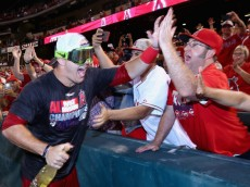 ANAHEIM, CA - SEPTEMBER 17:  Mike Trout #27 of the Los Angeles Angels of Anaheim celebrates with the fans after the Angels clinched the American League West Division at Angel Stadium of Anaheim on September 17, 2014 in Anaheim, California. The Angels defeated the Mariners 5-0.  (Photo by Jeff Gross/Getty Images)