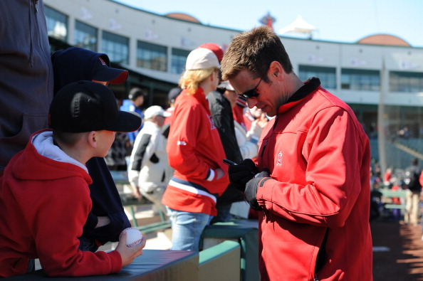 TEMPE, AZ - FEBRUARY 24:  Jerry Dipoto,  general manager of the Los Angeles Angels of Anaheim signs an autograph prior to the game against the Oakland Athletics on February 24, 2013 at Tempe Diablo Stadium in Tempe, Arizona. The Athletics defeated the Angels 7-5.  (Photo by Rich Pilling/Getty Images)