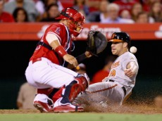 ANAHEIM, CA - JULY 22:  Chris Davis #19 of the Baltimore Orioles slides safely past catcher Hank Conger #24 of the Los Angeles Angels of Anaheim and scores a run in the sixth inning at Angel Stadium of Anaheim on July 22, 2014 in Anaheim, California.  (Photo by Jeff Gross/Getty Images)