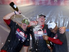 ANAHEIM, CA - SEPTEMBER 17:  (L-R) Mike Trout #27, Mike Butcher #23 and Erick Aybar #2 of the Los Angeles Angels of Anaheim celebrate with champagne after the Angels clinched the American League West Division at Angel Stadium of Anaheim on September 17, 2014 in Anaheim, California. The Angels defeated the Mariners 5-0.  (Photo by Jeff Gross/Getty Images)