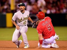ANAHEIM, CA - JUNE 13:  Marcus Semien #10 of the Oakland Athletics reacts as he tags out Albert Pujols #5 of the Los Angeles Angels attempting to steal second base during the sixth inning at Angel Stadium of Anaheim on June 13, 2015 in Anaheim, California.  (Photo by Harry How/Getty Images)