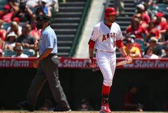 ANAHEIM, CA - JUNE 14:  Kyle Kubitza #18 of the Los Angeles Angels of Anaheim reacts after striking out swinging to end the fifth inning as home plate umpire Angel Hernandez #55 looks on during the MLB game against the Oakland Athletics at Angel Stadium of Anaheim on June 14, 2015 in Anaheim, California.  (Photo by Victor Decolongon/Getty Images)