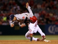 ANAHEIM, CA - JULY 06:  Shortstop Jose Iglesias #10 of the Boston Red Sox flips over Erick Aybar #2 of the Los Angeles Angels of Anaheim after tagging out Aybar at the end of a pickoff play at first in the 10th inning at Angel Stadium of Anaheim on July 6, 2013 in Anaheim, California.  (Photo by Stephen Dunn/Getty Images)