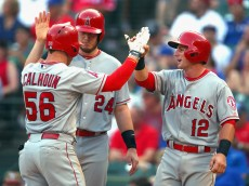 ARLINGTON, TX - JULY 05:  Kole Calhoun #56 of the Los Angeles Angels celebrates with C.J. Cron #24 of the Los Angeles Angels and Johnny Giavotella #12 of the Los Angeles Angels after hitting a three run home run against the Texas Rangers in the top of the fifth inning at Globe Life Park in Arlington on July 5, 2015 in Arlington, Texas.  (Photo by Tom Pennington/Getty Images)