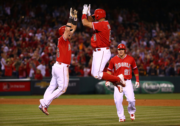 ANAHEIM, CA - MAY 25:  Kole Calhoun #56 and Albert Pujols #5 of the Los Angeles Angels of Anaheim celebrate after Pujols hit the game-winning RBI single to left field as teammate Mike Trout #27 looks on in the ninth inning against the San Diego Padres during the MLB game at Angel Stadium of Anaheim on May 25, 2015 in Anaheim, California. The Angels defeated the Padres 4-3.  (Photo by Victor Decolongon/Getty Images)