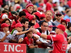 ANAHEIM, CA - JUNE 13:  Mike Trout #27 of the Los Angeles Angels signs autographs for fans before the game against the Oakland Athletics at Angel Stadium of Anaheim on June 13, 2015 in Anaheim, California.  (Photo by Harry How/Getty Images)