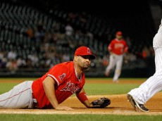 CHICAGO, IL - AUGUST 12: Albert Pujols #5 of the Los Angeles Angels of Anaheim watches the ball he was unable to catch at first base as Melky Cabrera #53 of the Chicago White Sox runs to second base at U.S. Cellular Field on August 12, 2015 in Chicago, Illinois.  (Photo by Jon Durr/Getty Images)