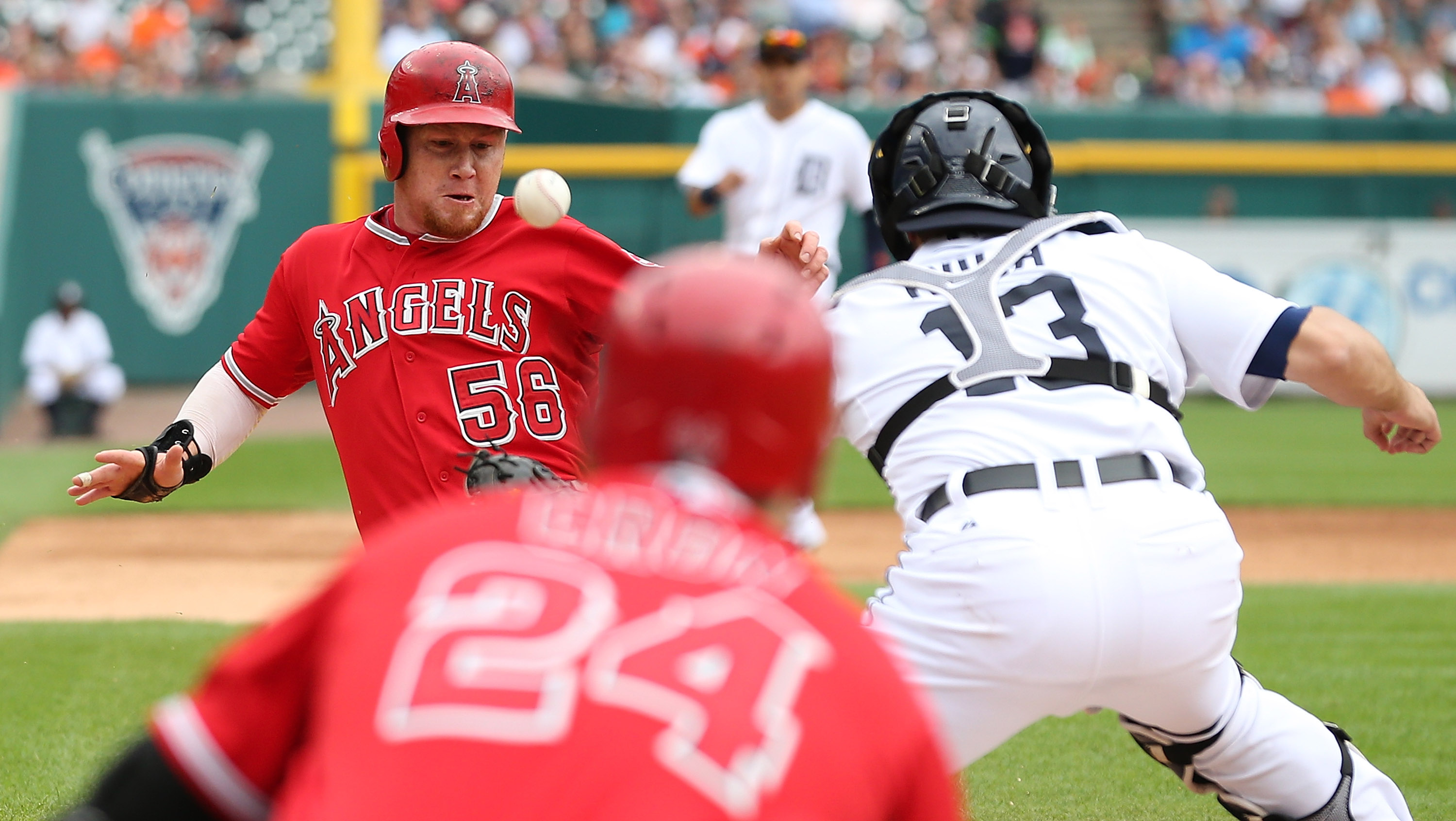 DETROIT, MI - AUGUST 27: Kole Calhoun #56 of the Los Angeles Angels scores on the single to left field by Albert Pujols #5 (not in photo) as Alex Avila #13 of the Detroit Tigers attempts to put on the tag during the sixth inning of the game on August 27, 2015 at Comerica Park in Detroit, Michigan. (Photo by Leon Halip/Getty Images)