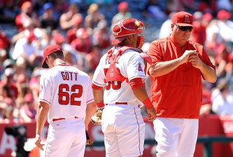 ANAHEIM, CA - JULY 26:  Trevor Gott #62 of the Los Angeles Angels of Anaheim is relieved by Manager Mike Scioscia #14  and Carlos Perez #58 in the seventh inning during a game against the Texas Rangers at Angel Stadium of Anaheim on July 26, 2015 in Anaheim, California.  (Photo by Jonathan Moore/Getty Images)