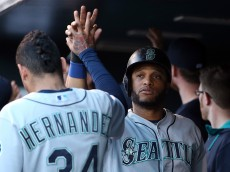 DENVER, CO - AUGUST 03:  Robinson Cano #22 of the Seattle Mariners celebrates after scoring with starting pitcher Felix Hernandez #34 of the Seattle Mariners in the first inning during interleague play at Coors Field on August 3, 2015 in Denver, Colorado.  (Photo by Doug Pensinger/Getty Images)