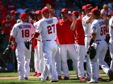 ANAHEIM, CA - SEPTEMBER 06:  (L-R)  Shane Victorino #18, Mike Trout #27 and Kole Calhoun #56 of the Los Angeles Angels of Anaheim celebrate with high-fives with their teammates after their 7-0 win against the Texas Rangers the MLB game at Angel Stadium of Anaheim on September 6, 2015 in Anaheim, California.  (Photo by Victor Decolongon/Getty Images)