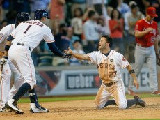 HOUSTON, TX - SEPTEMBER 23:  Jose Altuve #27 of the Houston Astros receives congratulations from Carlos Correa #1 and Jake Marisnick #6 aftefr scoring on a triple by George Springer #4 in the seventh inning against the Los Angeles Angels of Anaheim at Minute Maid Park on September 23, 2015 in Houston, Texas.  (Photo by Bob Levey/Getty Images)