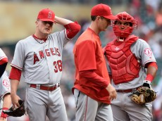 MINNEAPOLIS, MN - APRIL 17: Joe Smith #38 of the Los Angeles Angels of Anaheim reacts after pitching coach Charles Nagy #41 and catcher Carlos Perez #58 visit the mound during the ninth inning of the game on April 17, 2016 at Target Field in Minneapolis, Minnesota. The Twins defeated the Angels 3-2 in twelve innings. (Photo by Hannah Foslien/Getty Images)