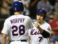 NEW YORK, NY - AUGUST 10: Travis d'Arnaud #7 of the New York Mets is congratulated by teammate Daniel Murphy #28 after scoring the tying run on a bases-loaded, hit-by-pitch to Curtis Granderson #3 against the Colorado Rockies during the seventh inning on August 10, 2015 at Citi Field in the Flushing neighborhood of the Queens borough of New York City. The Mets defeated the Rockies 4-2. (Photo by Rich Schultz/Getty Images)