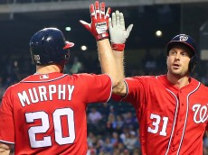 NEW YORK, NEW YORK - JULY 09: Max Scherzer #31 of the Washington Nationals is greeted by Daniel Murphy #20 after scoring on Ben Revere #9 RBI triple in the third inning against the New York Mets at Citi Field on July 9, 2016 in the Flushing neighborhood of the Queens borough of New York City.  (Photo by Mike Stobe/Getty Images)