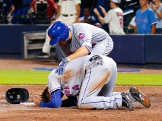 ATLANTA, GA - SEPTEMBER 10: Travis d'Arnaud #18 of the New York Mets checks on Wilmer Flores after Flores was involved in a collision at the plate (where he was out) against the Atlanta Braves during the eighth inning at Turner Field on September 10, 2016 in Atlanta, Georgia. The Braves won 4-3 in extra innings. (Photo by Kevin Liles/Getty Images)