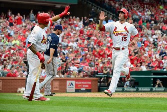 ST. LOUIS, MO - APRIL 16: Randal Grichuk #15 of the St. Louis Cardinals is congratulated by Kolten Wong #16 after scoring during the eighth inning against the Milwaukee Brewers at Busch Stadium on April 16, 2015 in St. Louis, Missouri.  (Photo by Jeff Curry/Getty Images)
