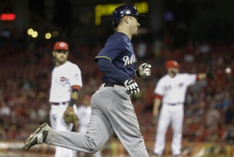 Milwaukee Brewers' Aaron Hill, center, smiles as he runs home after hitting the go-ahead grand slam off Cincinnati Reds relief pitcher Caleb Cotham in the tenth inning of a baseball game, Saturday, May 7, 2016, in Cincinnati. (AP Photo/John Minchillo)