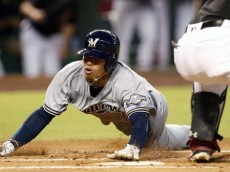 The Milwaukee Brewers' Orlando Arcia (left) scores a run on a sacrifice fly out by Hernan Perez against the Arizona Diamondbacks in the first inning Saturday, Aug. 6, 2016, in Phoenix.