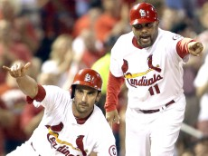 St. Louis Cardinals' Matt Carpenter, left, celebrates after hitting a triple while Cardinals third base coach Jose Oquend points during the third inning of a baseball game against the Pittsburgh Pirates on Friday, Sept. 6, 2013, in St. Louis. (AP Photo/Jeff Roberson)