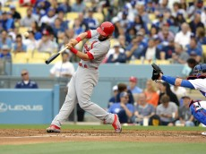 St. Louis Cardinals' Matt Carpenter, left, hits a solo home run as Los Angeles Dodgers catcher Yasmani Grandal watches during the third inning of a baseball game, Sunday, May 15, 2016, in Los Angeles. (AP Photo/Mark J. Terrill)