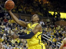 Michigan forward Glenn Robinson III makes a layup as Arizona center Kaleb Tarczewski (35) looks on during the first half of an NCAA college basketball game in Ann Arbor, Mich., Saturday, Dec. 14, 2013. (AP Photo/Carlos Osorio)