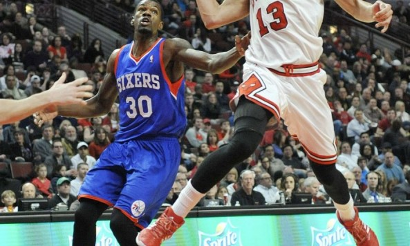 Joakim Noah passes the ball while being guarded by Dewayne Dedmon